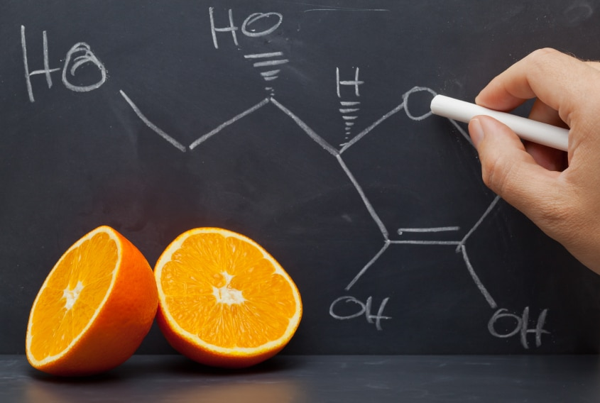 An orange and a chemical formula. being drawn in chalk on a blackboard